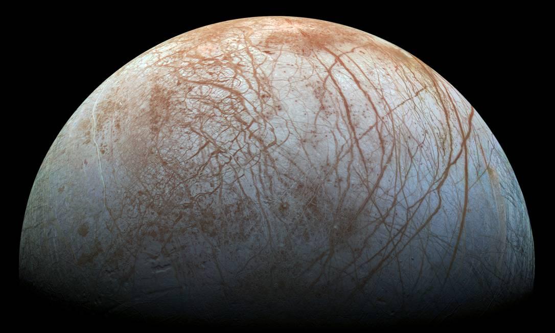 Imagem da lua joviana de Europa obtida pela sonda Galileo, da Nasa, mostra a sua superfície congelada cortada por fissuras que ligariam o oceano sob a crosta de gelo ao espaço externo Foto: Nasa