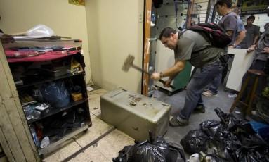 Policial quebra um cofre encontrado num dos boxes do camelódromo da Uruguaiana: 150 mandados de busca e apreensão, expedidos pela Justiça, foram cumpridos Foto: Márcia Foletto / Agência O Globo