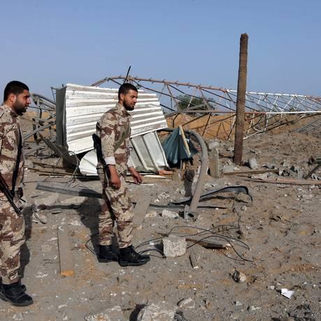 Membros das forças de segurança palestinas leais ao Hamas no local atingido por ataque aéreo em Rafah, na Faixa de Gaza Foto: Ibraheem Abu Mustafa / Reuters