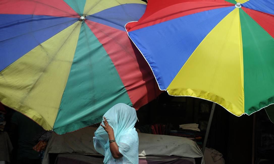 Em Calcutá, mulher protege a cabeça do sol forte Foto: DIBYANGSHU SARKAR / AFP