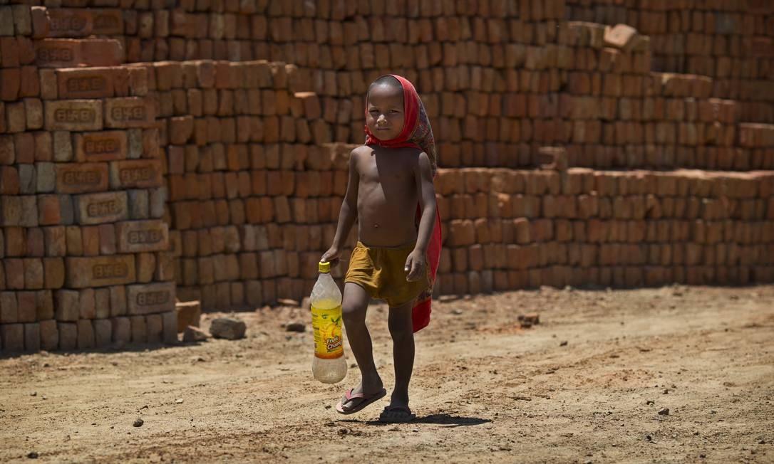 Menino caminha até uma bomba de água para encher sua garrafa em Ghasera, nos arredores de Nova Délhi Foto: Saurabh Das / AP