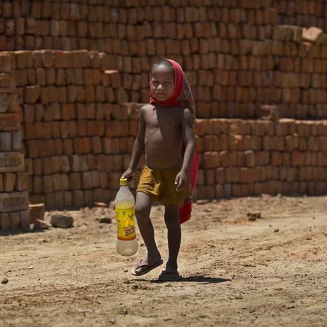 Um menino, filho de um operário, caminha até uma bomba de água para encher sua garrafa em um dia quente de verão em Ghasera, nos arredores de Nova Délhi, na Índia Foto: Saurabh Das / AP