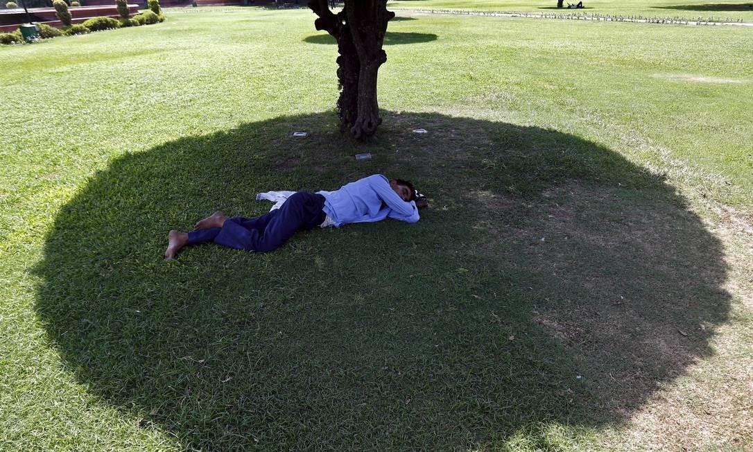 Homem descansa sob a sombra de uma árvore em parque da capital indiana Foto: ANINDITO MUKHERJEE / REUTERS