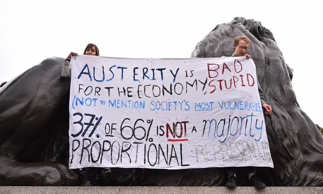 Manifestantes sobem em um dos leões de Trafalgar Square para exibir uma faixa contra medidas de austeridade BEN STANSALL / AFP