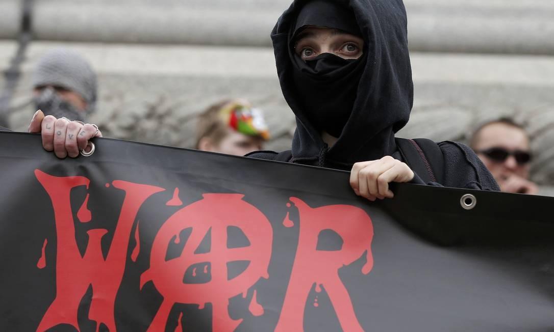 Com máscara, o manifestante protesta após o discurso da rainha Foto: PETER NICHOLLS / REUTERS