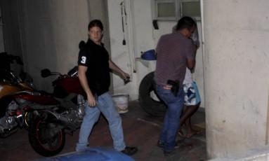Policiais escoltam adolescente de 15 anos (de bermuda estampada azul) na chegada à DH, na Barra da Tijuca Foto: Pedro Teixeira / Agência O Globo