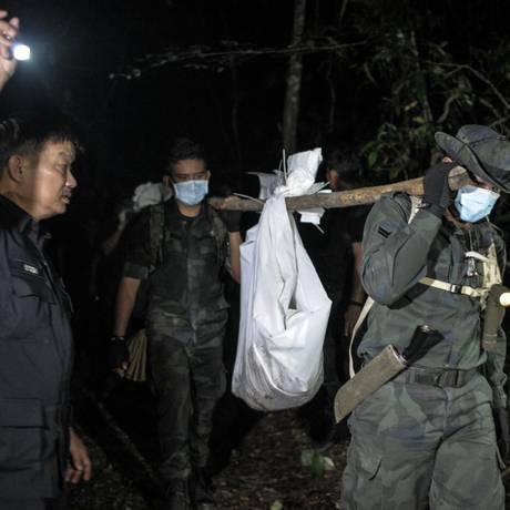 Polícia malaia transporta restos humanos encontrados em acampamentos de contrabandistas Foto: MOHD RASFAN / AFP