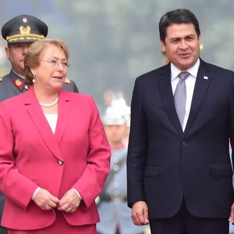 Presidente do Chile, Michelle Bachelet, e seu colega hondurenho, Juan Orlando Hernández, recebem honras militares na chegada ao palácio presidencial La Moneda, em Santiago Foto: MARTIN BERNETTI / AFP