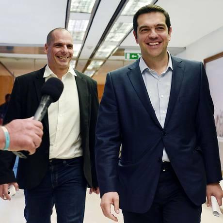 O primeiro-ministro grego, Alexis Tsipras, sorri ao lado do ministro das Finanças, Yanis Varoufakis, ao sair de uma reunião em Atenas Foto: LOUISA GOULIAMAKI / AFP