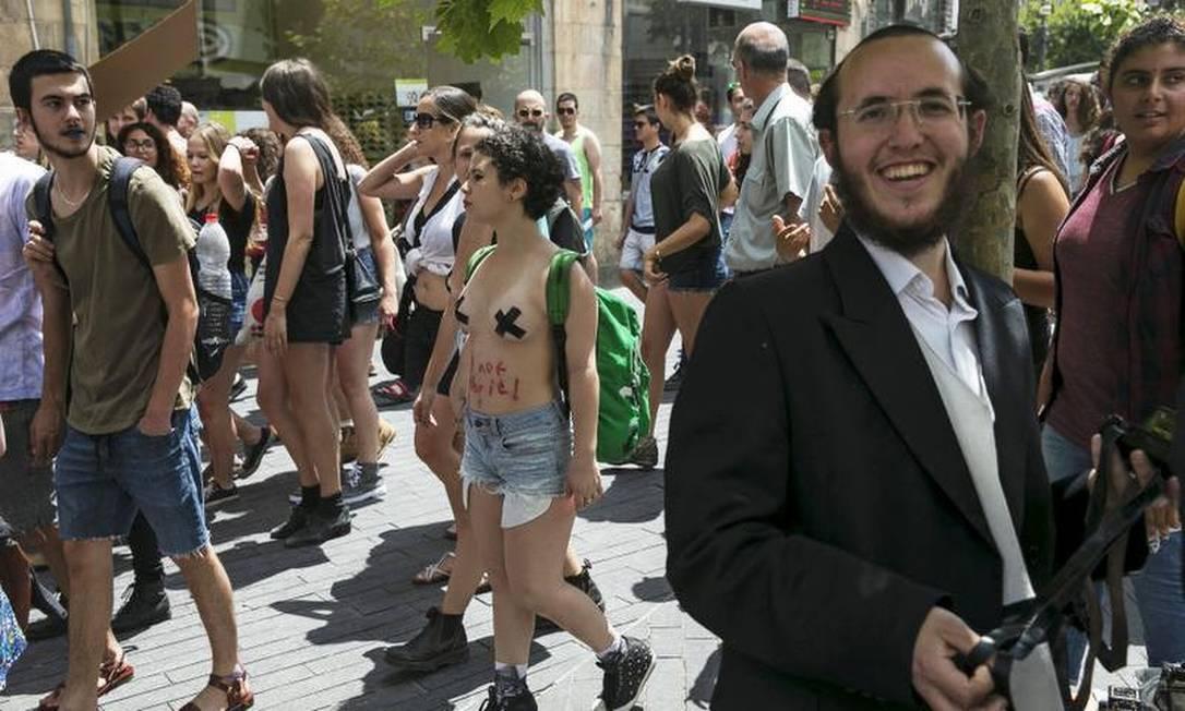 Manifestantes passam por um judeu ultra-ortodoxo nas ruas de Jerusalém AFP