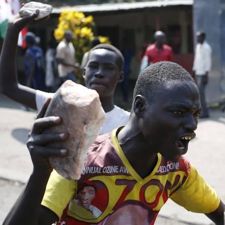 Um manifestante protesta nesta terça-feira com uma pedra contra a decisão do presidente Pierre Nkurunziza de concorrer ao terceiro mandato, em Bujumbura Foto: Goran Tomasevic / Reuters