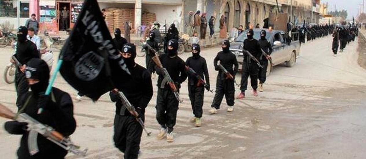 Membros do Estado Islâmico marchando em Raqqa, na Síria. Grupo tem recebido apoio de organizações menores na África e no Sudeste Asiático. Fluxo de comabatentes estrangeiros levou a reforma de sistema de triagem e análise de dados de passageiros de aviões Foto: Uncredited / AP