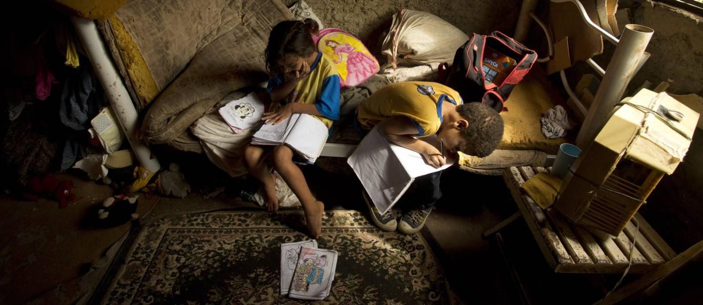 Diana, de 6 anos, e Adriel, de 8, estudam na casa erguida à beira de um rio em Belford Roxo, na Baixada Fluminense Foto: Márcia Foletto / Agência O Globo