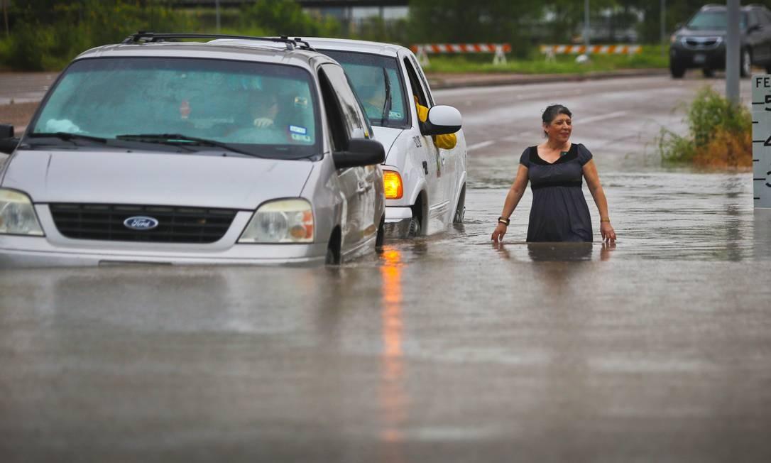 Motoristas e pedestres tentam seguir por estrada unindada em Brownville, no Texas. Presidente americano assinou declaração de catástrofe e governo federal irá liberar fundos para ajudar áreas do estado afetadas por tempestades Foto: Yvette Vela / AP