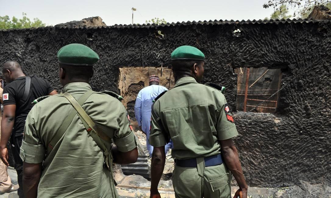 Policiais nigerianos examinam casa incendiada no estado de Borno, no Nordeste do país. Boko Haram voltou a realizar ataques na região, que deixaram pelo menos 11 mortos Foto: - / AFP