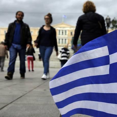 Pedestres caminham na Praça Syntagma, em Atenas Foto: Thanassis Stavrakis / AP