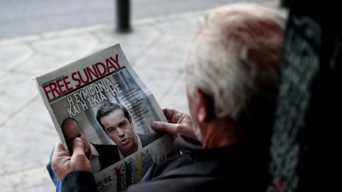 Expectativa. Homem lê jornal com foto do premier Alexis Tsipras em Atenas Foto: ANGELOS TZORTZINIS / ANGELOS TZORTZINIS/AFP