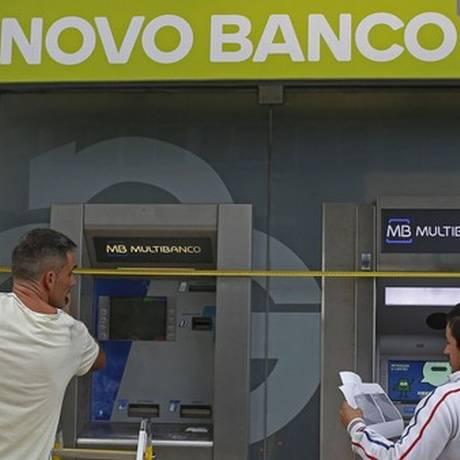 Funcionários instalam máquinas eletrônicas do Novo Banco Foto: Reuters