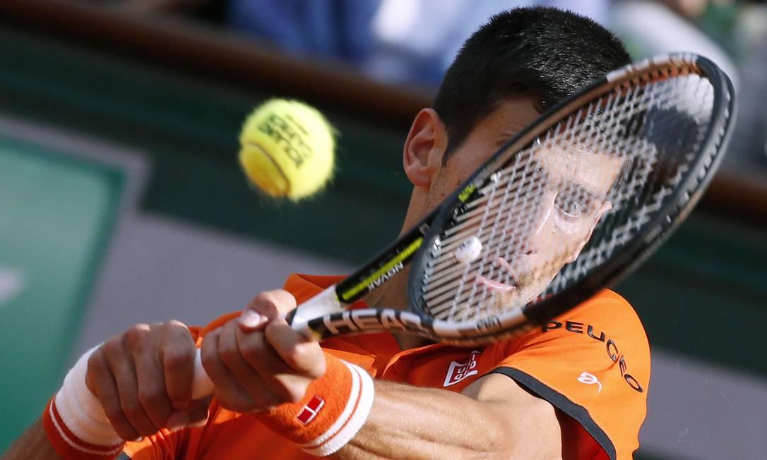 O sérvio Novak Djokovic retorna a bola para o francês Richard Gasquet, durante a quarta rodada do Aberto de Tênis de Paris PATRICK KOVARIK / AFP