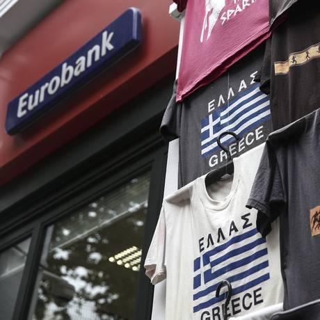 Loja de souvenir vende camisetas com o tema da Grécia ao lado de uma filial do Eurobank em Atenas Foto: Yorgos Karahalis / Bloomberg