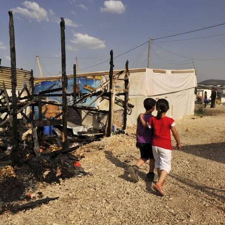 Crianças andam perto dos restos de tendas que foram queimadas em um campo de refugiados sírios no Líbano Foto: HASSAN ABDALLAH / REUTERS