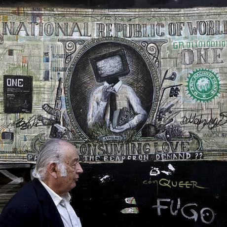Homem caminha diante de grafite de uma nota de dollar em Atenas Foto: ALKIS KONSTANTINIDIS / REUTERS