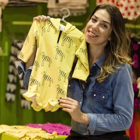 Paula mostra uma das peças da nova linha da marca: roupas cheia de cores e desenhos Foto: Guilherme Leporace / Agência O Globo