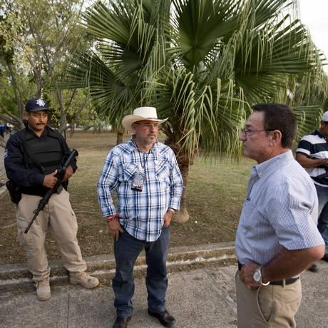 Hipólito Mora, ao centro, espera para começar um encontro de campanha com moradores de Coahuayana. O candidato é cercado por dois seguranças armados Foto: Eduardo Verdugo / AP