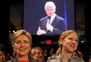 Hillary e sua filha, Chelsea, observam Bill fazer um discurso em Nova York durante reunião da Inciativa Global: de festas íntimas com líderes mundiais a acordos com o peso do Estado americano Foto: Stephen Hilger / BLOOMBERG NEWS