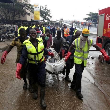 Equipes de resgate carregam corpos após explosão em posto de gasolina em Acra Foto: STAFF / REUTERS