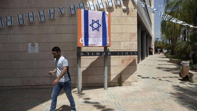 Logo nacionalista. Funcionários de empresa parceira da Orange em Israel taparam colocaram uma bandeira do país em cima do logo da empresa: justificativa foi comercial Foto: Dan Balilty / AP
