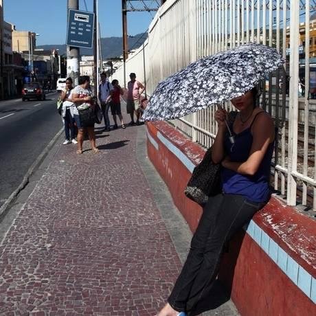 Passageiros usam guarda-chuvas para evitar sol forte Foto: Agência O Globo / Angelo Antônio Duarte