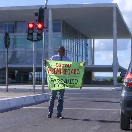 Eudes do Carmo Pereira da Silva, de 42 anos, caminha por entre os carros em frente ao Palácio do Planalto para pedir emprego Foto: ANDRE COELHO / Agência O Globo