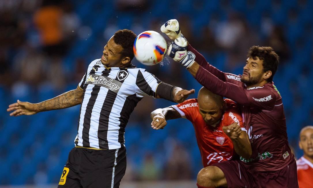 Bill, do Botafogo, divide a bola com o goleiro Daniel, do Mogi Daniel Marenco / Agência O Globo