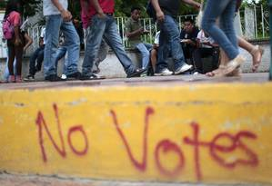 Pessoas caminham por uma calçada perto uma pixação convocando ao boicote eleitoral Foto: Pedro PARDO / AFP