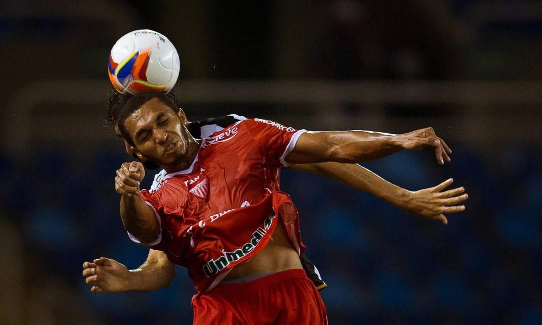 Renan Fonseca, do Botafogo, disputa a bola no ar com atacante do Mogi Daniel Marenco / Agência O Globo