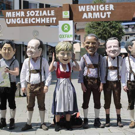 Grupo protesta contra reunião do G7, que começa neste domingo, na Alemanha, usando máscares do primeiro-ministro da Itália, Matteo Renzi; o do Japão, Shinzo Abe; do presidente francês Francois Hollande; da chanceler alemã e anfitriã do encontro, Angela M Foto: Markus Schreiber / AP