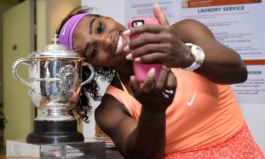 Já no vestiário, Serena faz selfie com o troféu conquistado no torneio Corinne Dubreuil / AP