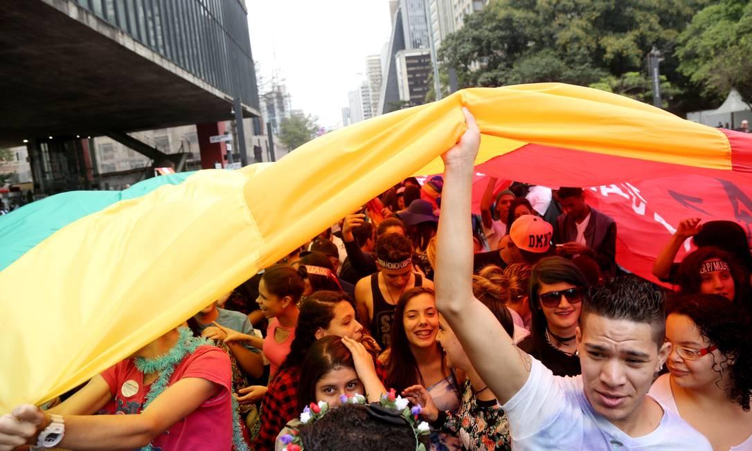 Jovens carregam enorme bandeira com as cores do arco-íris, símbolo do movimento LGBT Fernando Donasci / Agência O Globo