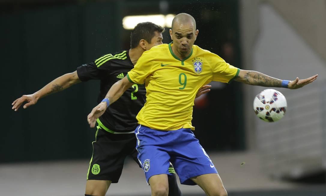 Diego Tardelli disputa a bola com o mexicano Julio Dominguez no amistoso em São Paulo Nelson Antoine / AP