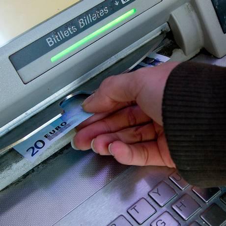 Cliente saca € 20 de um caixa eletrônico em Barcelona Foto: David Ramos/20-3-2013 / Bloomberg News