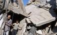 Homem e menino palestinos observam os destroços causados pelos ataques israelenses em resposta ao Hamas