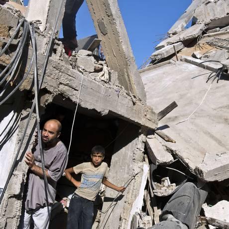 Homem e menino palestinos observam os destroços causados pelos ataques israelenses em resposta ao Hamas Foto: ROBERTO SCHMIDT / AFP