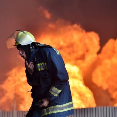 Bombeiros tentam conter incêndio em um depósito de combustível, na vila de Kryachki, cerca de 30 km ao sudoeste de Kiev Foto: SERGEI SUPINSKY / AFP