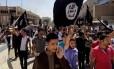 Foto de arquivo de junho de 2014 mostra manifestantes entoando slogans a favor do Estado Islâmico enquanto acenam bandeiras do grupo, em frente à sede do governo provincial de Mossul, no Iraque