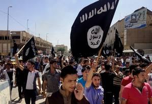 Foto de arquivo de junho de 2014 mostra manifestantes entoando slogans a favor do Estado Islâmico enquanto acenam bandeiras do grupo, em frente à sede do governo provincial de Mossul, no Iraque Foto: Uncredited / AP