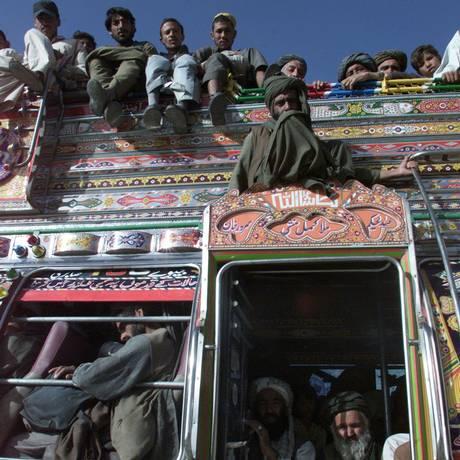 Paquistaneses se aglomeram nos antigos ônibus do país. Muitos ficam, inclusive, no teto do coletivo Foto: REUTERS / Zahid Hussein