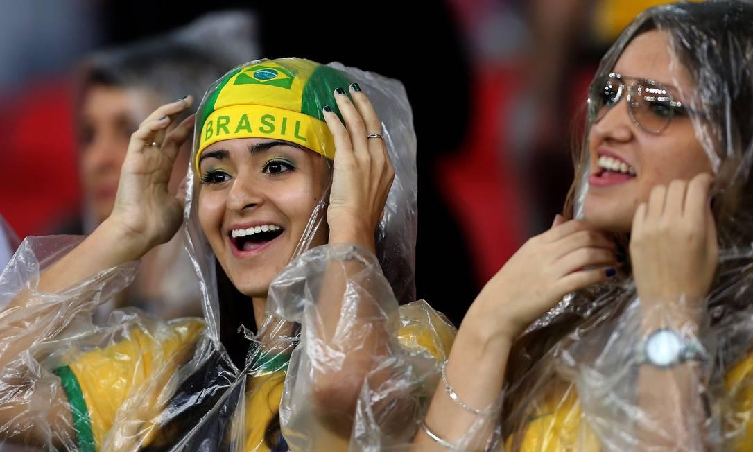 Dupla de torcedoras se protege da chuva no Beira-Rio JEFFERSON BERNARDES / AFP