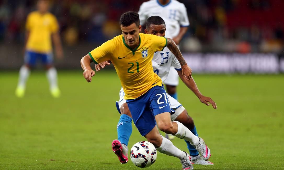Philippe Coutinho tenta pasar pela marcação do jogador de Honduras JEFFERSON BERNARDES / AFP