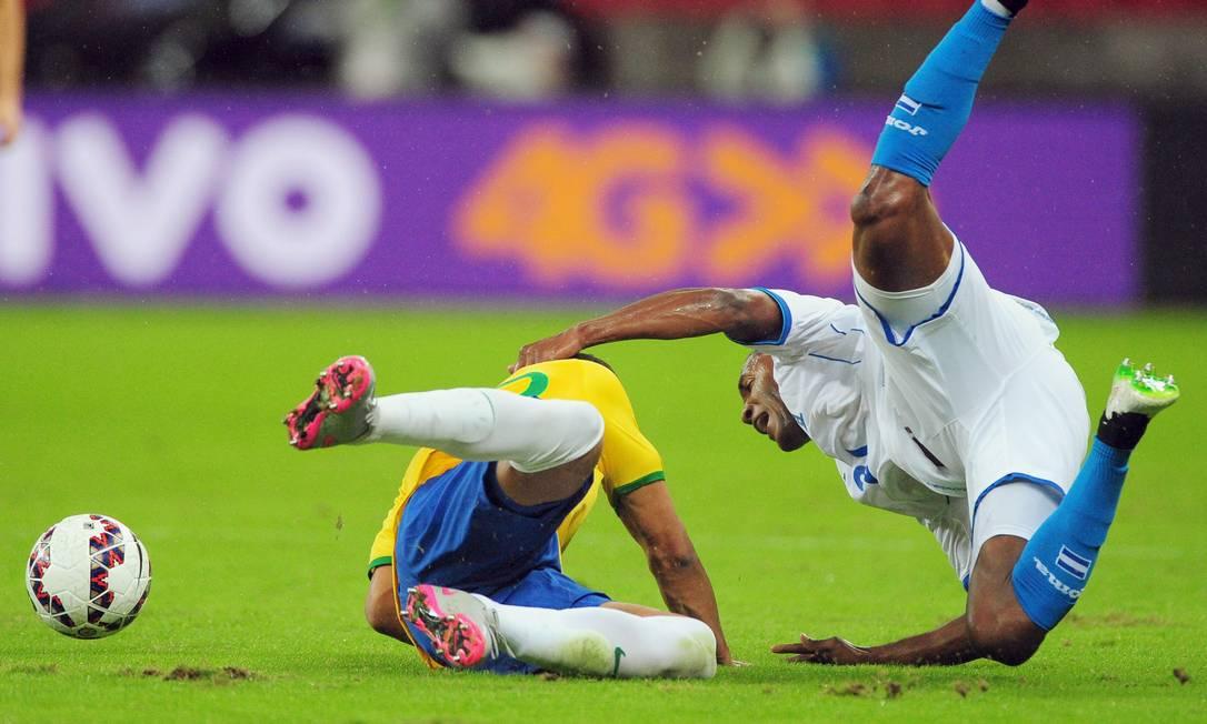Casemiro e o hondurenho Beckeles caem no gramado em Porto Alegre EDISON VARA / REUTERS